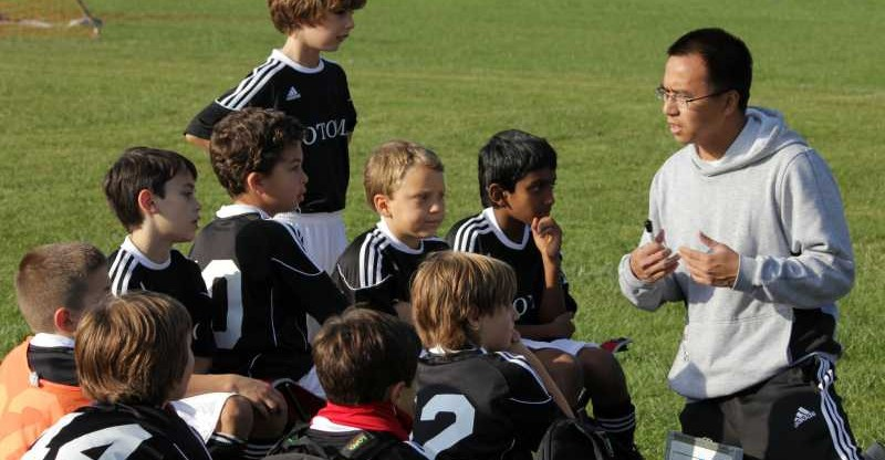 a coach talks to soccer players