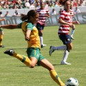 a woman soccer player kicks a ball