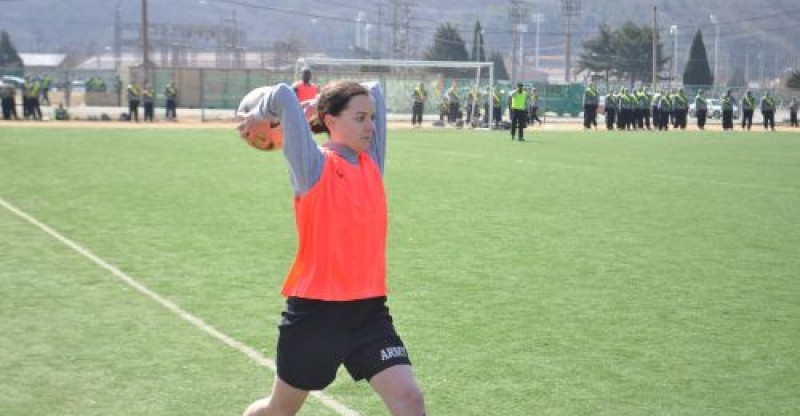an army soccer player takes a throw in