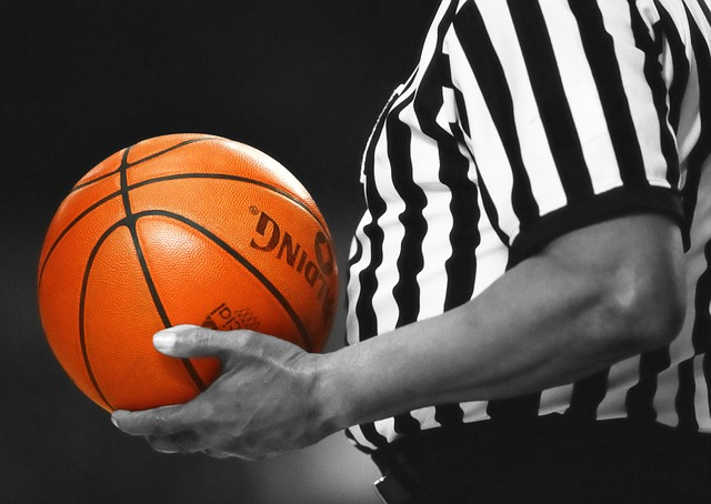 a basketball referee holds a ball