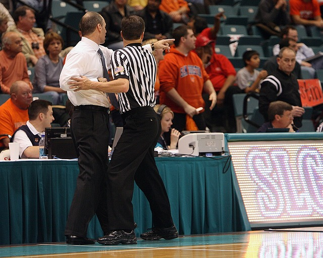 a basketball referee interacts with a coach